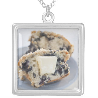 A blueberry muffin with butter silver plated necklace