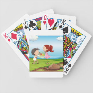 A boy making a marriage proposal at the riverbank bicycle playing cards