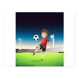 A boy playing soccer alone postcard