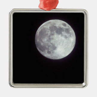 A bright full moon in a black night sky. Silver-Colored square decoration