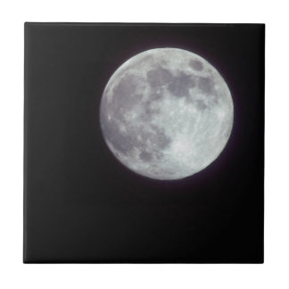 A bright full moon in a black night sky tile