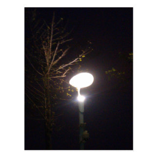 A bright lamp defeating the darkness of night postcard