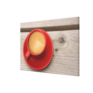 A bright red cup of espresso coffee on a picnic stretched canvas prints