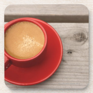 A bright red cup of espresso coffee on a picnic coaster