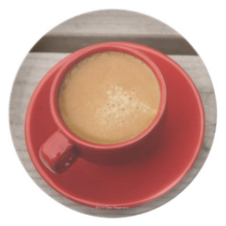 A bright red cup of espresso coffee on a picnic plate