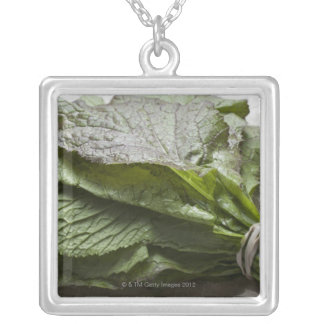 A bunch of fresh mustard greens, from a farmer's silver plated necklace