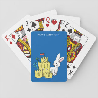 A bunny and a sandcastle playing cards