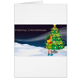 A card with an elf facing the christmas tree