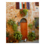 A cat seeks entrance to home in Pienza, Italy. Posters