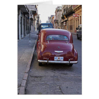 A classic old red Peugeot car parked on a street Card