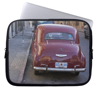 A classic old red Peugeot car parked on a street Laptop Sleeve