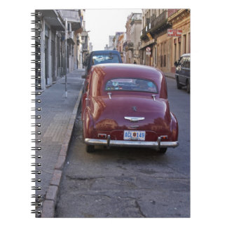 A classic old red Peugeot car parked on a street Notebook