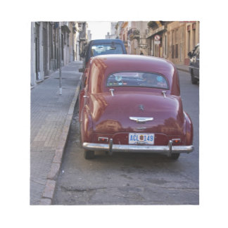 A classic old red Peugeot car parked on a street Notepad