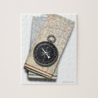A compass sitting on a stack of folded road maps jigsaw puzzle