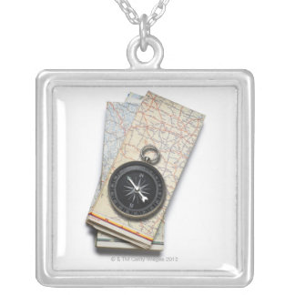 A compass sitting on a stack of folded road maps silver plated necklace