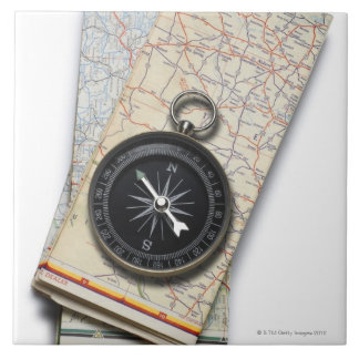 A compass sitting on a stack of folded road maps tile