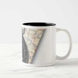 A compass sitting on a stack of folded road maps Two-Tone coffee mug