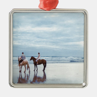 A couple riding horses on Parkiri beach in New Silver-Colored Square Decoration