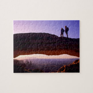 A couple watches sunrise from atop Mesa Arch in Puzzles