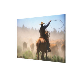 A cowboy out working the herd on a cattle canvas print