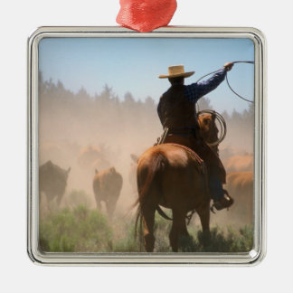A cowboy out working the herd on a cattle christmas ornament