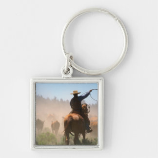 A cowboy out working the herd on a cattle key ring