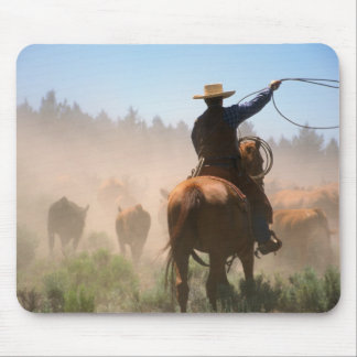 A cowboy out working the herd on a cattle mouse mat