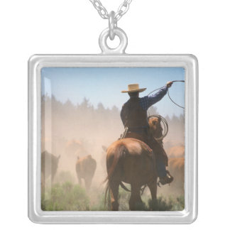A cowboy out working the herd on a cattle silver plated necklace