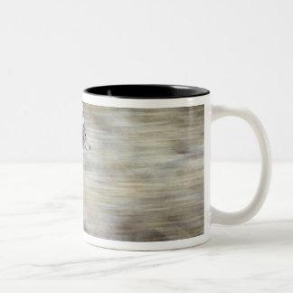 A coyote runs through the hillside blending into coffee mugs