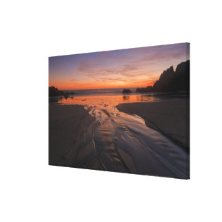 A crescent moon sets through a dusk-colored sky canvas print