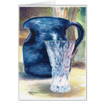 A crystal glass and a blue pitcher