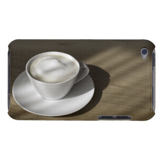 A cup of cappuccino coffee lies on an oak barely there iPod cases