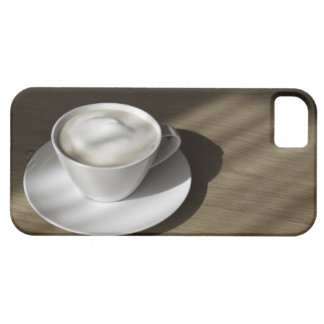 A cup of cappuccino coffee lies on an oak case for the iPhone 5
