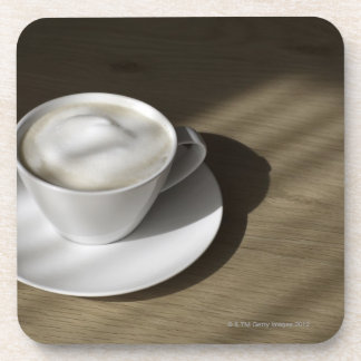 A cup of cappuccino coffee lies on an oak coasters