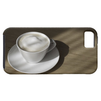A cup of cappuccino coffee lies on an oak iPhone 5 case