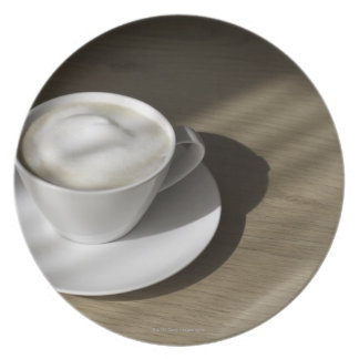 A cup of cappuccino coffee lies on an oak plate