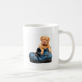 A cute little brown puppy posing over a blue shoe basic white mug