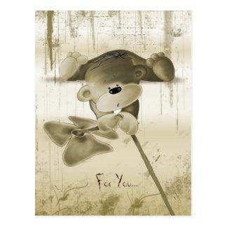 A cute teddy bear with a flower - postcard
