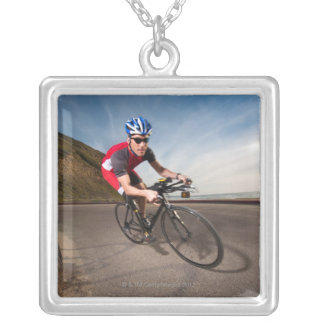 A cyclist leaning into a corner silver plated necklace