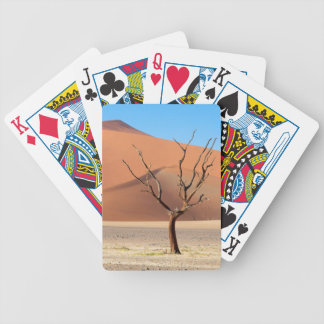 A dead tree on a desert plain with dunes bicycle playing cards