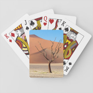 A dead tree on a desert plain with dunes playing cards