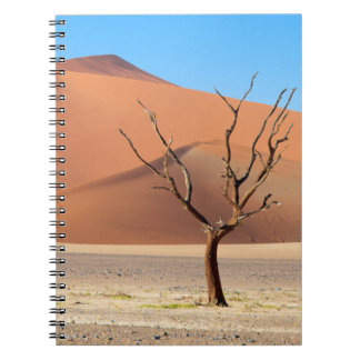 A dead tree on a desert plain with dunes spiral notebook