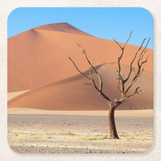 A dead tree on a desert plain with dunes square paper coaster