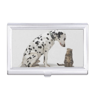 A dog looking at a cat business card holder