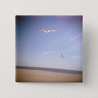 a dreamy image of seagulls flying at the beach 15 cm square badge