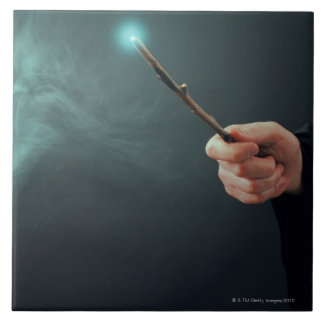 A fantasy wizard making magic with wand. tile