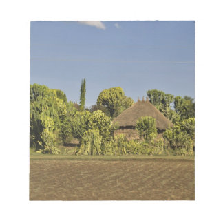 A farmed field in front of thatched roof houses notepad