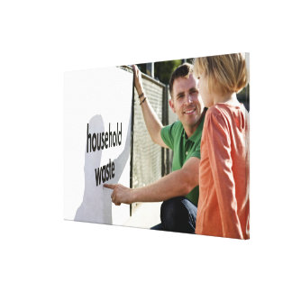 A father teaching his daughter about recycling canvas print