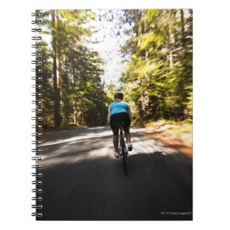 A female cyclist quickly rides on a small narrow notebook