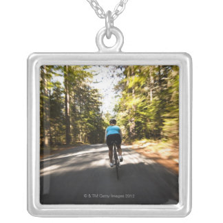 A female cyclist quickly rides on a small narrow silver plated necklace